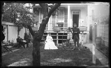 USA: View of back garden looking onto house and back porch with two men and a woman