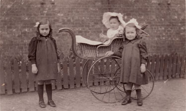 Unidentified group of children with pram