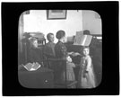 View: c11611 USA, Bay Ridge: Woman and children around a piano while she plays